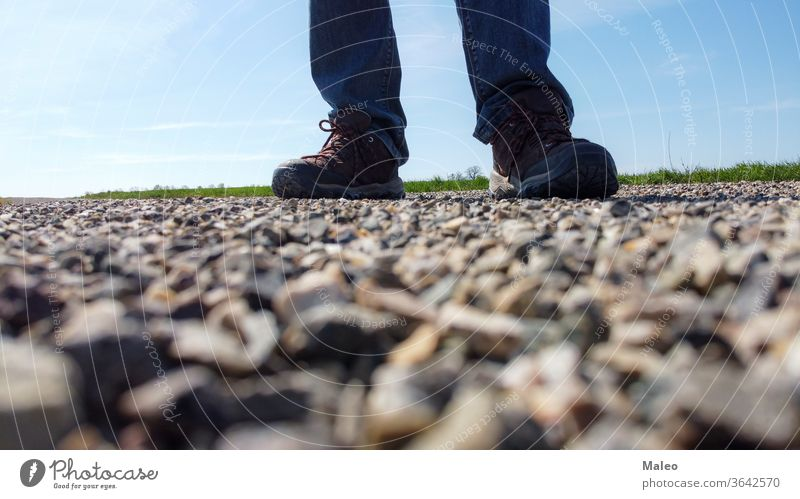 Legs of a man in sneakers stand on a gravel road day top view cobbled feet leg outdoor people rock shoes sidewalk standing stone texture travel arriving beach