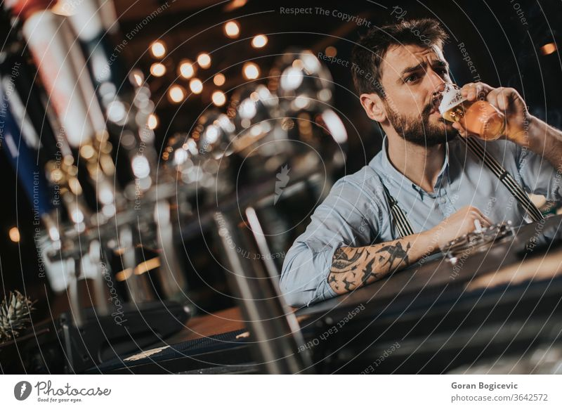 Man drinking beer and smoking cigarette at pub in the night club alcohol bad bar beard casual caucasian concept cool drunk glass guy habit handsome indoors male