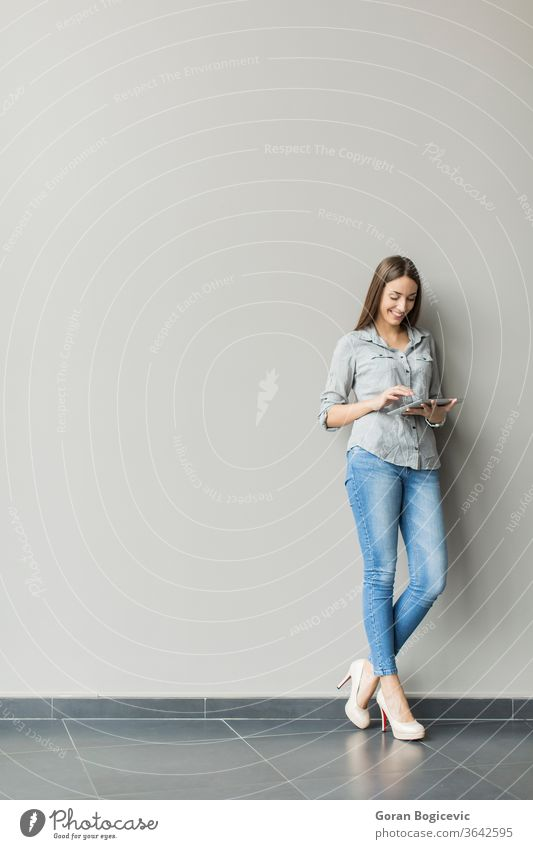 Woman with tablet by the wall adult casual caucasian communication computer contemporary copyspace digital display grey female handsome internet woman cute
