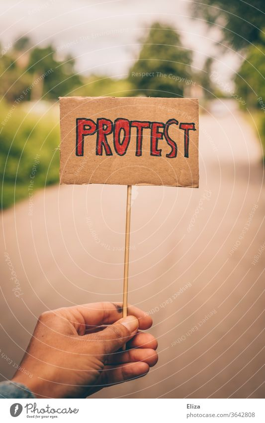 One hand holds a sign with the word protest. Concept demonstration, resistance. Demonstration on the other hand rejecting Protest demonstrate by hand anti