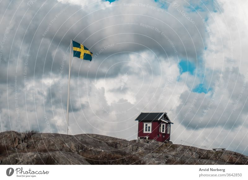 A traditional red and white small hut next to Swedish flag in Gothenburg southern archipelago, Sweden baltic beautiful beauty black blue cloud clouds coast