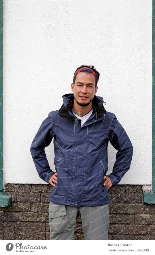 Young man in hiking outfit in front of white wall adult attractive bandana casual caucasian copy space face fashion guy handsome jacket lifestyle male model