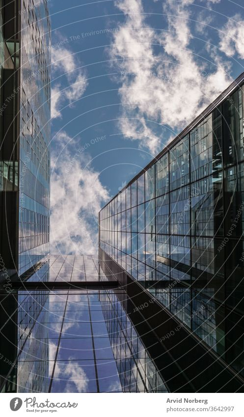 Looking up on a building with reflecting glass windows angle architecture background blue buildings business city cityscape clouds commercial corporate district