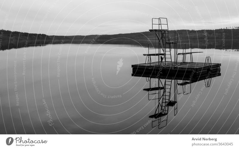 Black and white jetty jump tower with 1, 2 and 3 meter height in a rural lake in Sweden with reflection abstract amazing art background beach beautiful black