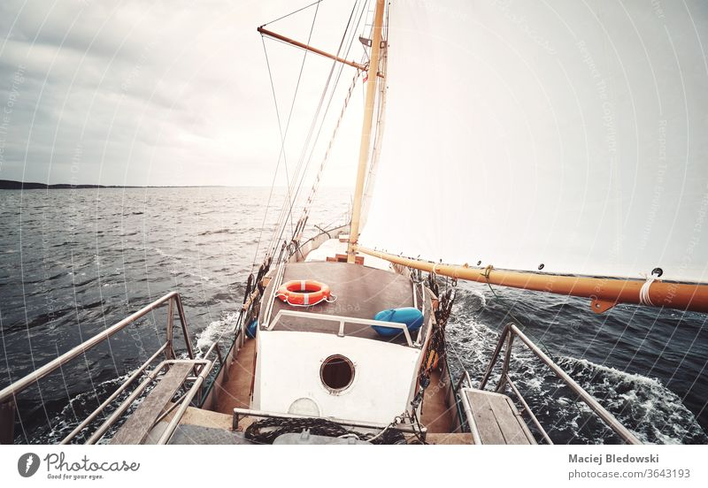 Sailing against the sun, color toned picture of an old schooner. sailing boat adventure vacation mast water sea ocean freedom deck retro vintage sunset faded