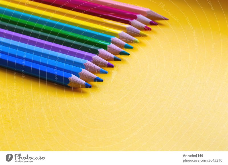 Colored pencils in Rainbow colors in a row on orange background, retro modern design space for text drawing school colorful education white yellow art green