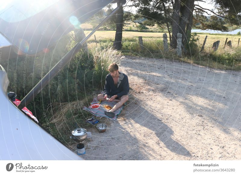 young man sits on a dirt road and prepares a picnic break on the road again Young man Picnic Vacation & Travel In transit off off the beaten track Freedom