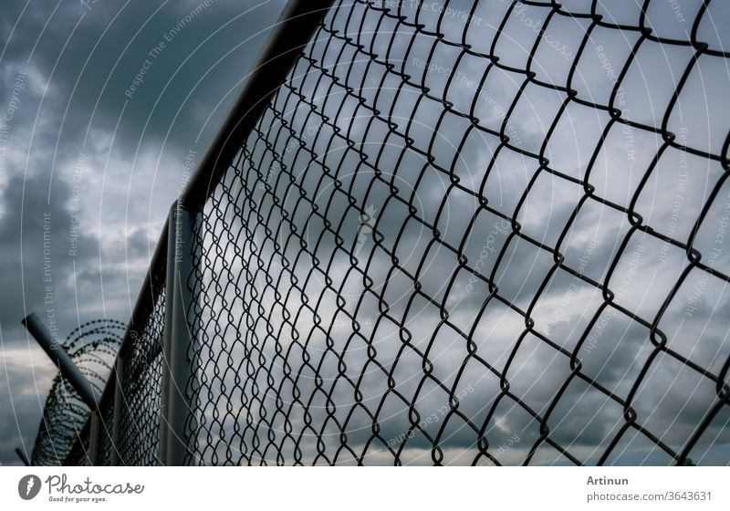 Military zone mesh fence. Prison security fence. Looking up view of barbed wire security fence with storm sky and dark clouds. Razor wire jail fence. Barrier border. Boundary security wall.