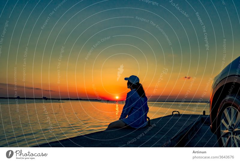 Lonely young woman wear a cap relaxing on the beach alone in front of the car with orange and blue sky at sunset. Summer vacation and travel concept. thailand
