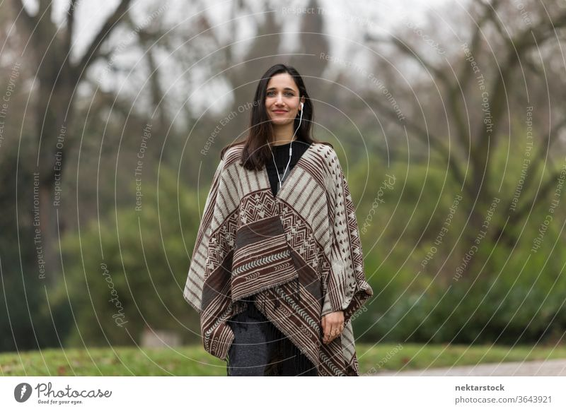 Young woman with tanned complexion wearing poncho in park and smiling. young woman Indian ethnicity middle eastern ethnicity earphones medium shot audiobook