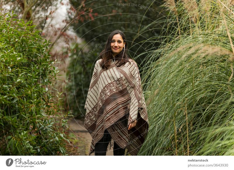 Young woman wearing poncho posing between tall grass in autumn. young woman Indian ethnicity middle eastern ethnicity earphones medium shot audiobook