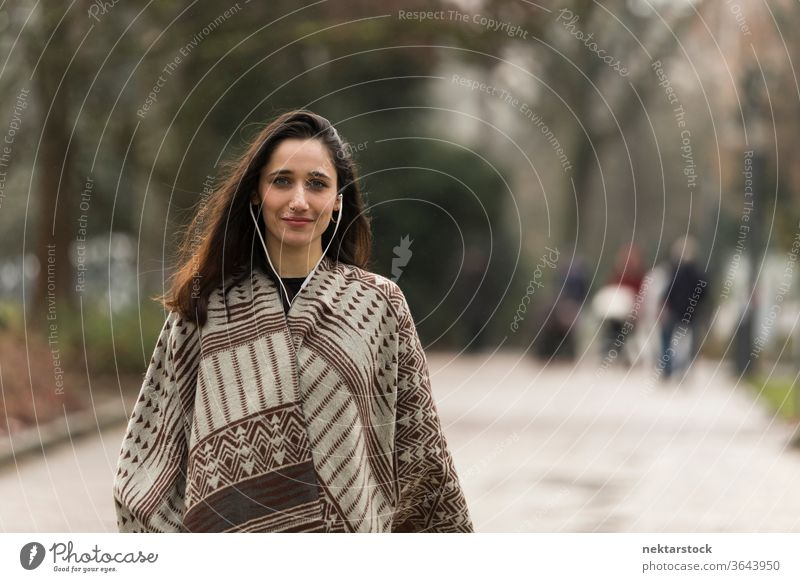 Young Indian woman wearing poncho and earphones smiling for the camera outdoors. Medium shot. young woman Indian ethnicity middle eastern ethnicity medium shot