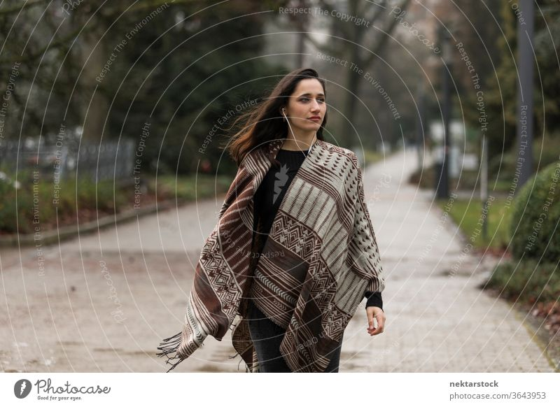 Young Indian woman wearing poncho walking outdoors with head turned looking away. young woman Indian ethnicity middle eastern ethnicity earphones medium shot