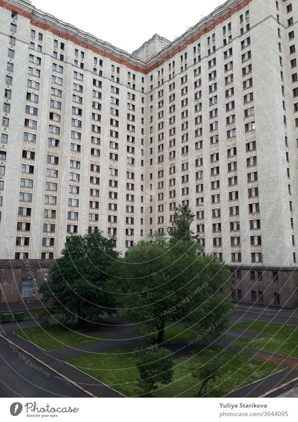 Photo of a tall block of flats with balconies in Moscow. Living apartments building architecture background. Common house object with gray walls and windows. Dormitory of Moscow State University.