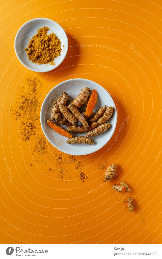 Turmeric roots in a bowl and powder on an orange background. Top view, healthy food. turmeric Root Yellow Curcuma Herbs and spices Colour photo Orange