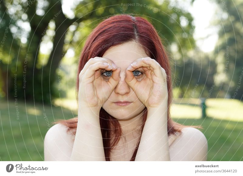 Hands imitating binoculars Observe Search Looking Surveillance see Binoculars Eyeglasses Spy hands Woman girl youthful Outdoors Nature portrait red hair Summer