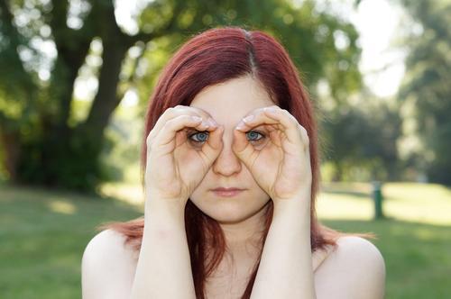 Hands imitating binoculars Observe Search Looking Surveillance see Binoculars Eyeglasses Spy hands Woman girl youthful Outdoors Nature portrait red hair Summer