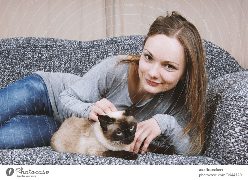 happy young woman relaxing on sofa with cat pet girl affection couch stroke stroking cuddle cuddling petting female adult blonde casual jeans denim smile