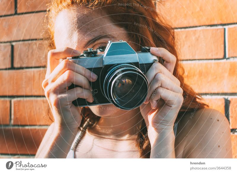 young woman holds an analog camera and looks through the viewfinder antiquated antique antiquity classic classical click close up electronic equipment film