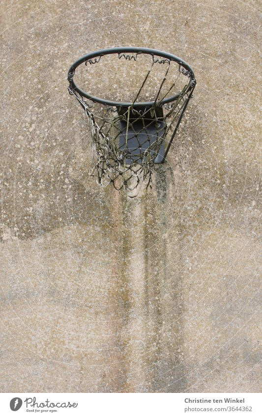 Old worn out basketball hoop with tattered net hangs on an old weathered concrete wall Basketball basket basketball net Net Broken shredded Concrete wall