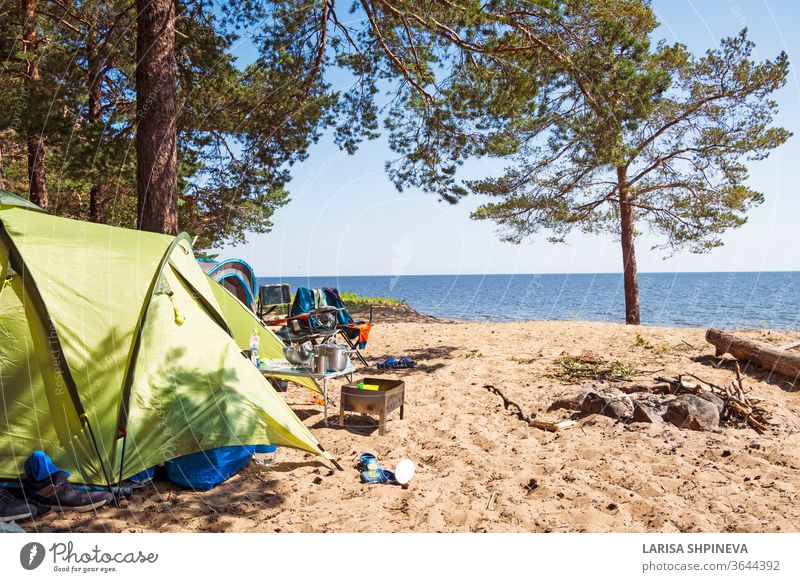 Camping and tent on the beach sea under the pine forest on the shore of the Gulf of Finland, St. Petersburg, Russia. Concept of outdoor activities, healthy lifestyle