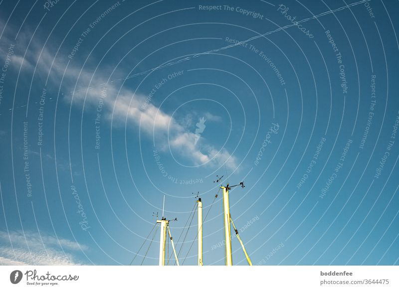 Tips of three white sailing masts with radio tracking and radar systems against a blue sky with feather cloud and contrails, both crossing each other Blue sky