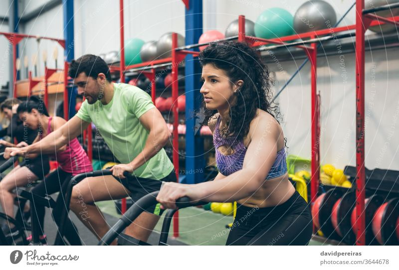 Athletes doing air bike indoor woman training group cross fit gym cross-training bicycle endurance power female person young people women fitness