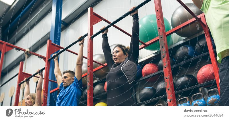 Athletes ready to do pull ups in the box group rack cross fit hanging bar wod workout of the day exercise banner panorama panoramic web fitness sport chin ups