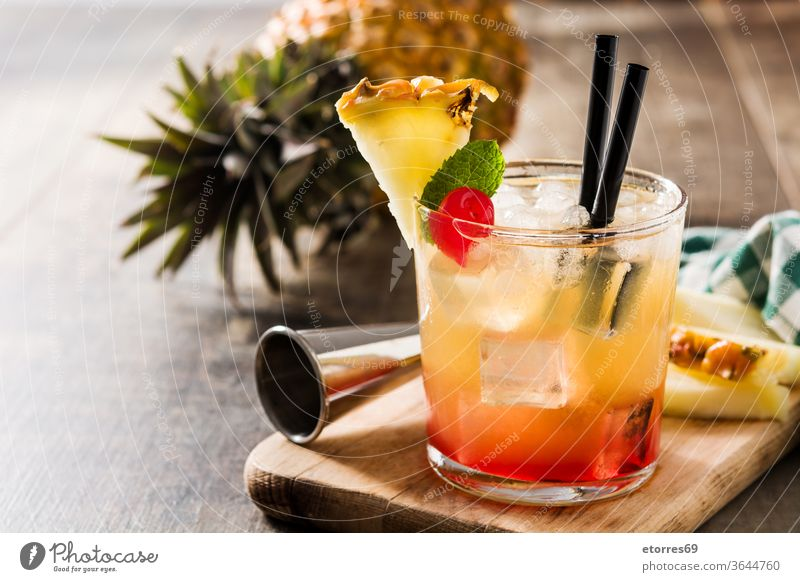 Cold mai tai cocktail with pineapple and cherry alcoholic beverage booze cold delicious drink food fresh fruit glass juice lime mix refreshment rum sweet syrup