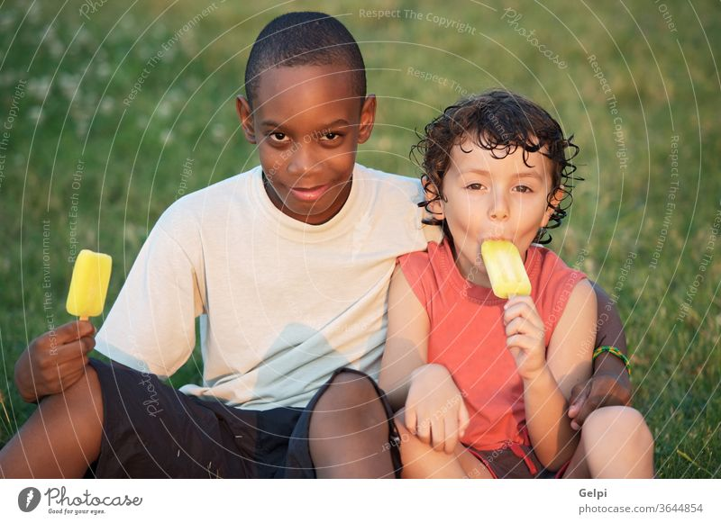 A couple of friends african appetite background black boy caucasian child children clear cold concept conceptual cream delicious dessert eat eating enjoy ethnic