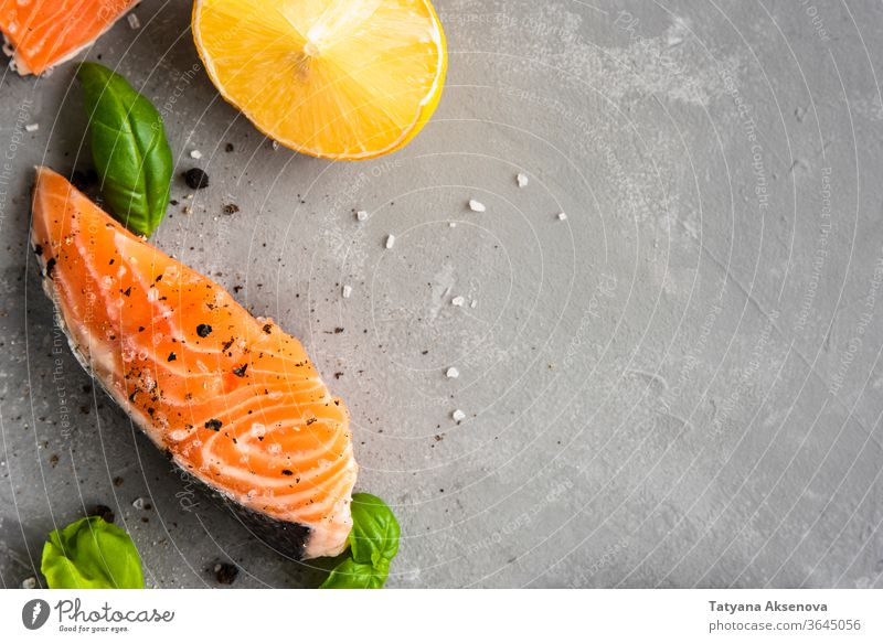 Salmon fillet piece with lemon, salt salmon fish food raw fresh healthy steak seafood cooking slice closeup pepper omega ingredient trout delicious nutrition