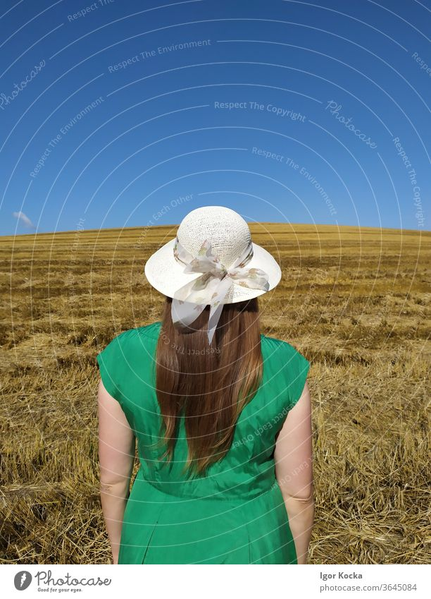 Rear View Of Woman Standing On Land Field Rear view Summer Clear sky Green Dress Hat Meadow Landscape Beautiful weather Freedom Lifestyle Copy Space