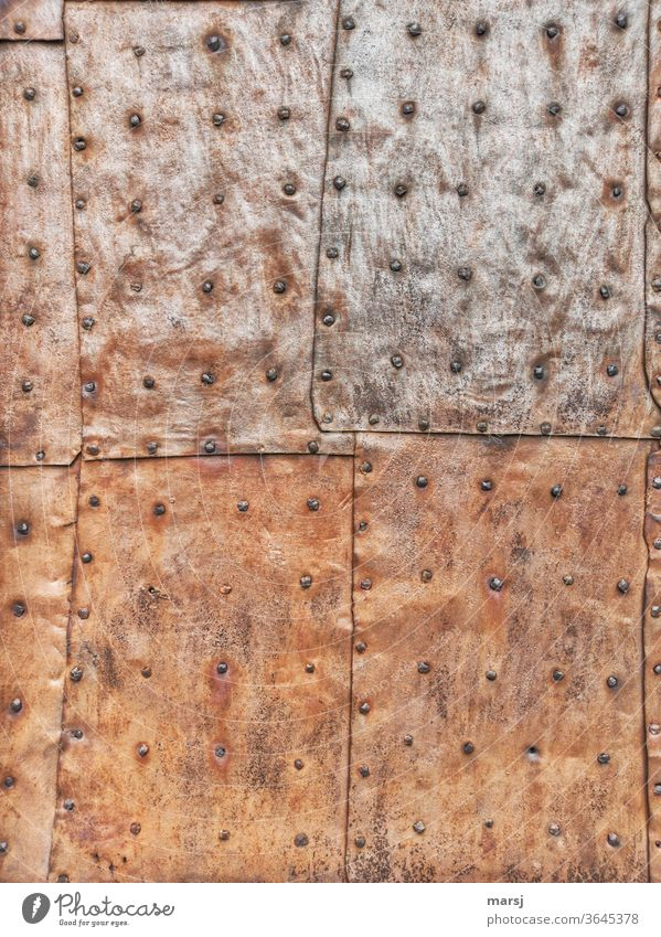 Riveted sheet iron panels that protect a door from the weather patchwork Tin Iron Stud Rust rusty metal Protection lap overlap Wallpapers Patina Oxydation Metal
