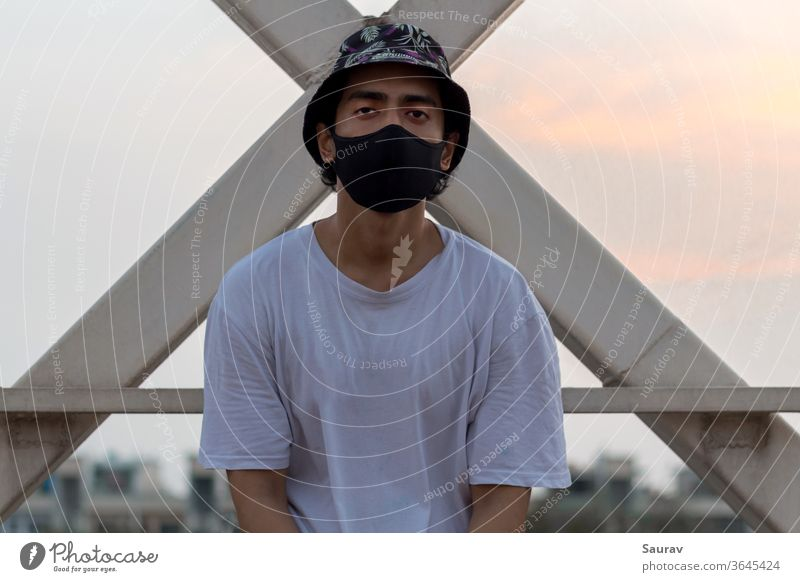 A young male put a protective face mask on to avoid Corona Virus infection in a city while wearing a floral bucket cap and a white t-shirt.. coronavirus
