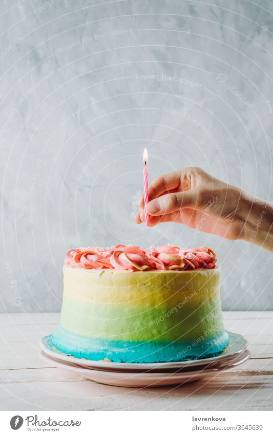 Closeup of colorful vegan cake and woman's hand holding birthday candle above it, selective focus fingers hands female homemade fresh blue pink happy decoration