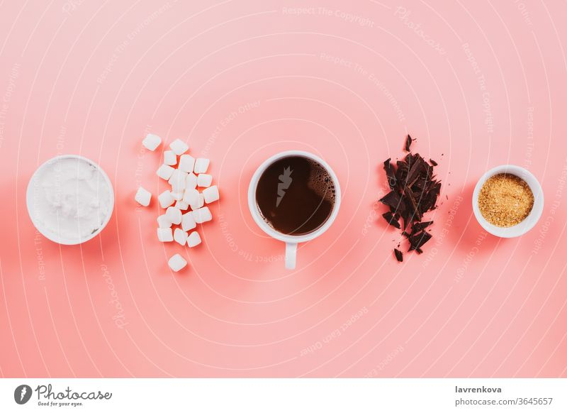 Flatlay of vegan cocoa, chocolate, coconut cream, sugar and vegetarian marshmallows on pink fall winter autumn ingredient flat cozy flatlay table cafe cup