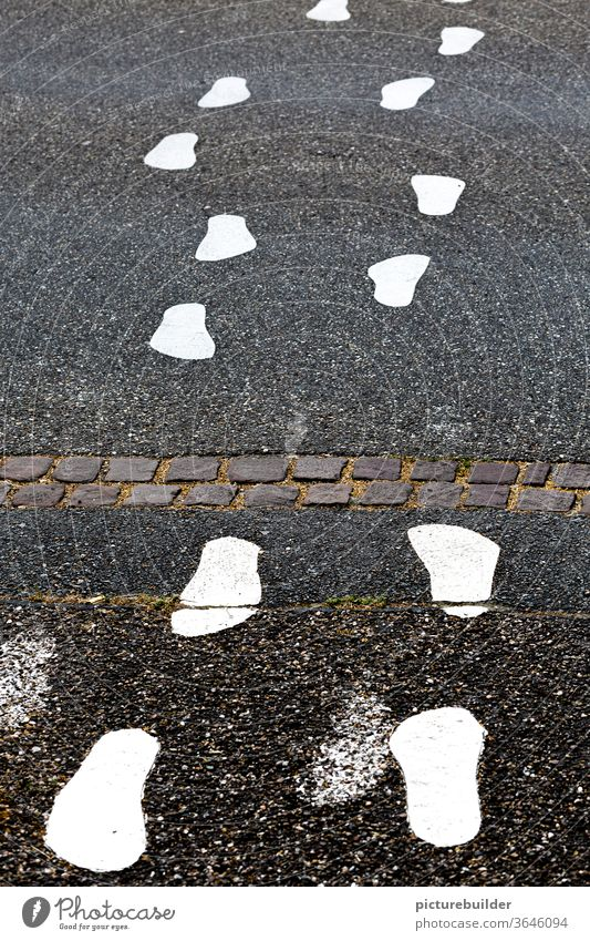 White footprints on the asphalt of the road footsteps Street Asphalt Exterior shot Deserted Signs and labeling Colour photo Transport Lanes & trails Gray