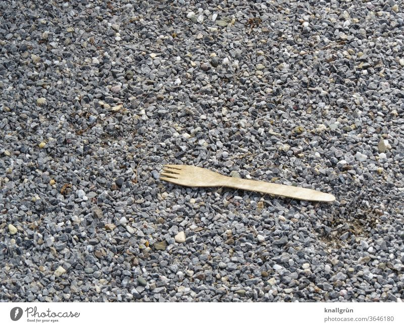 Organic disposable cutlery fork made of wood lies on road gravel Organic produce ecologic Environment environmental awareness Sustainability Nutrition natural