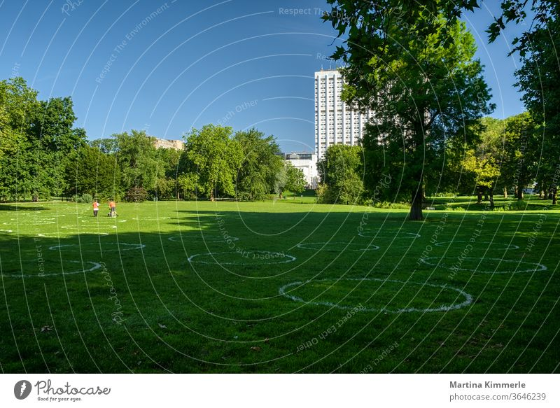 Chalk circles on the lawn in a park to keep the minimum distance. Social distancing. Corona, Covid19 in Rotterdam. keep sb./sth. apart activity tree huts