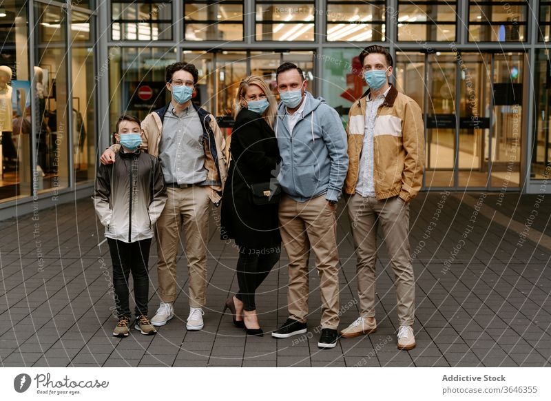 Positive friends in face masks against glass building relative respirator content positive door modern hand in pocket style coronavirus covid 19 boy child