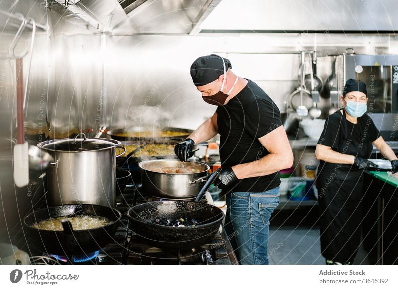 Focused male chef in face mask chef preparing meal woman respirator focus serious kitchen restaurant coronavirus ingredient food cook cooking busy glove