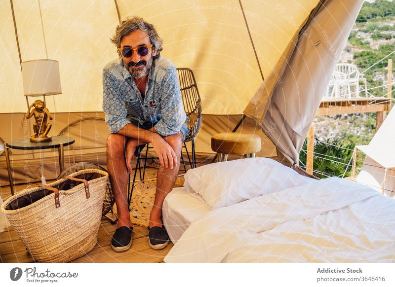 Cheerful man resting in traveling camp traveler content mature relax cozy resort creative glad comfort chair campsite summer sunglasses smile casual enjoy happy
