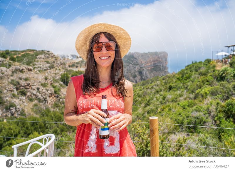 Happy woman with bottle of beer in tent traveler camp happy cheerful resort sunglasses cozy sunny leisure beverage relax content glad comfort summer mature
