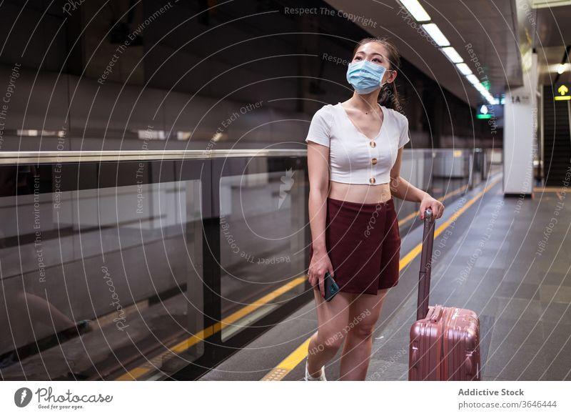 Stylish Asian woman in respirator with suitcase waiting for train railway station walk travel stand platform coronavirus passenger covid 19 epidemic skirt young