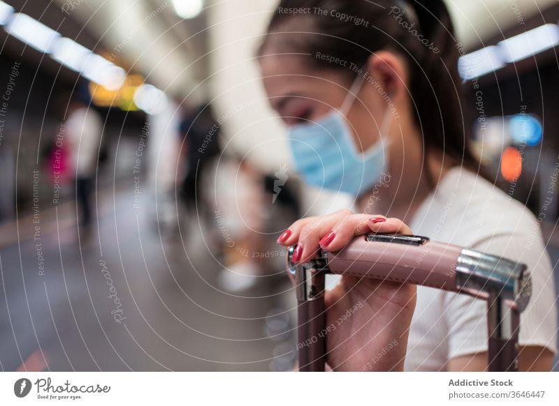 Asian woman in mask waiting for train rail link suitcase station travel respirator coronavirus covid 19 epidemic passenger bench skirt asian ethnic young female