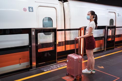 Asian woman in respirator waiting to board train in station railway station suitcase travel platform coronavirus calm cabin passenger covid 19 epidemic mask