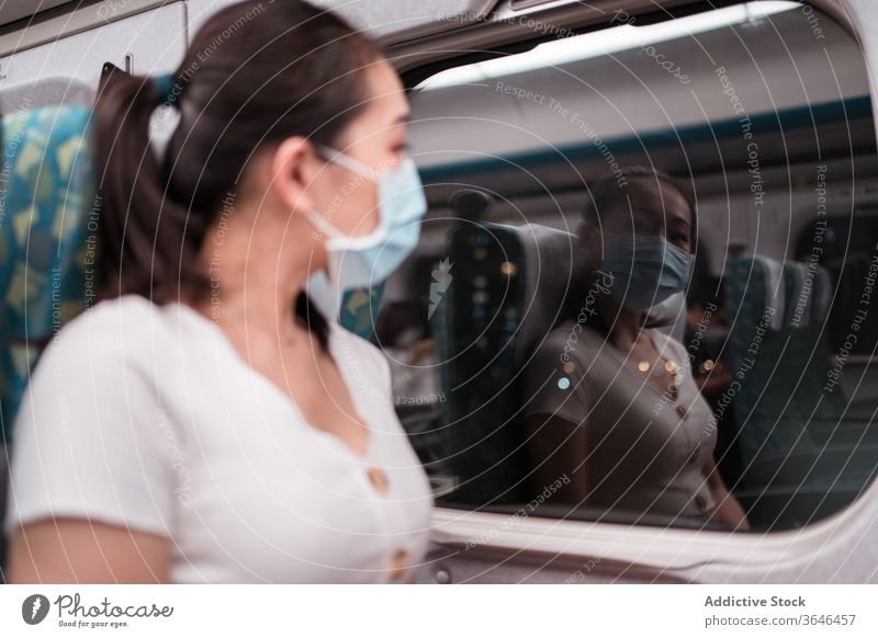 Calm female train passenger in respirator looking out window woman reflection cabin at night trip mask coronavirus comfort commute departure thoughtful