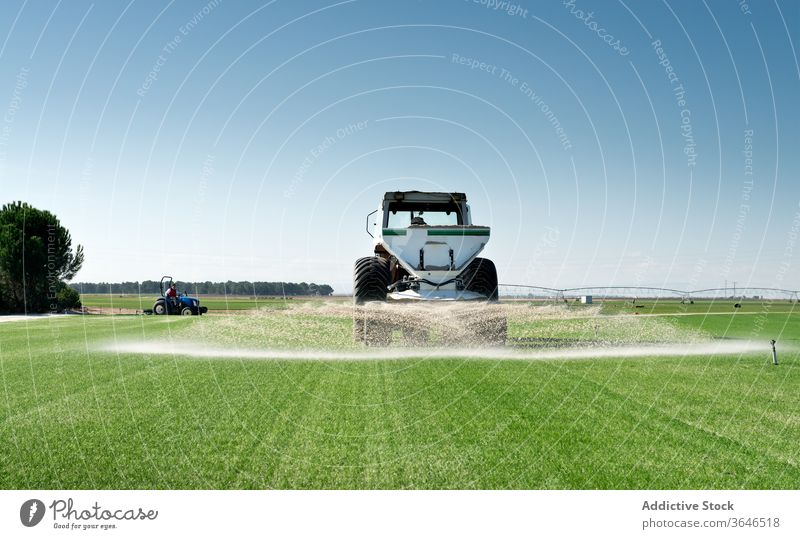 Industrial tractor watering agricultural field agriculture machine green grass countryside nature rural meadow industrial summer farm vehicle landscape daytime