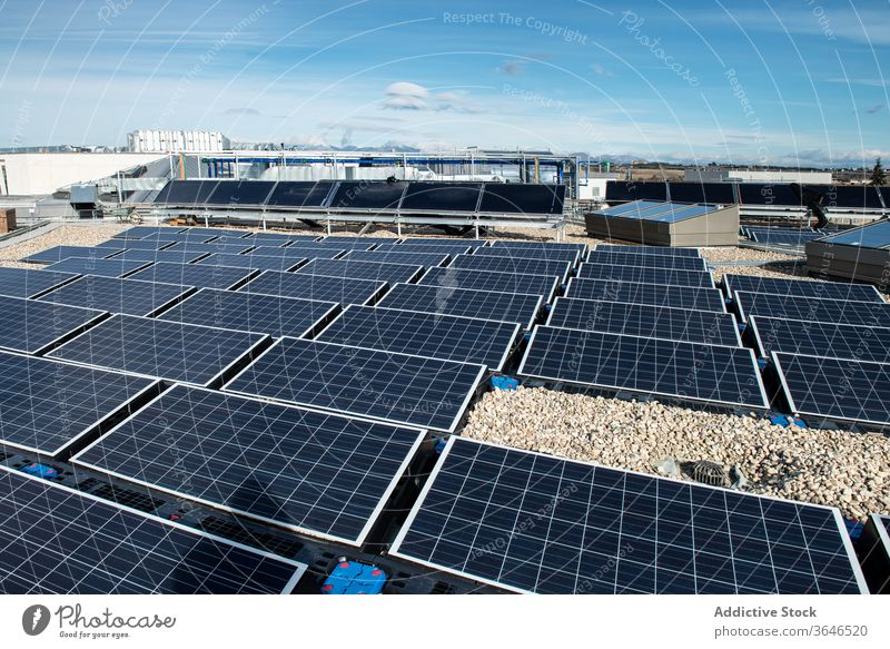 Solar panels on roof of building solar battery alternative renewal energy resource ecology sustainable contemporary construction daytime sun sunny rooftop