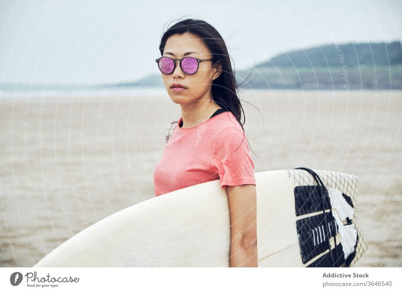 Content female surfer walking on beach with surfboard woman sandy carry content sea casual seaside carefree activity young sporty tranquil lifestyle sunglasses